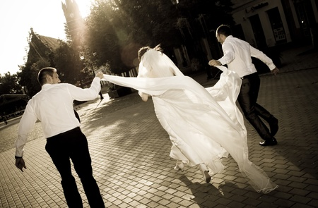 getting a bride: Bride running away with two man Stock Photo