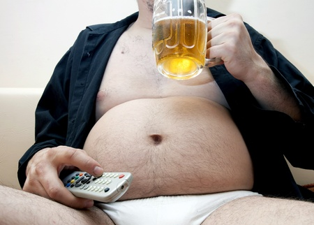 man couch: Overweight man sitting on the couch with a beer glass and remote control