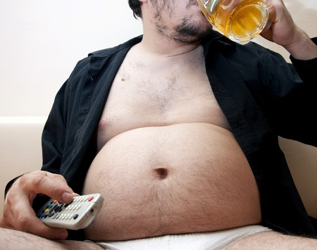 abusive man: Overweight man sitting on the couch with a beer glass and remote control