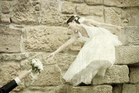 Vintage photograph of bride reaching for her bouquet