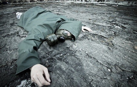 Man with gas mask fallen on the ground  photo