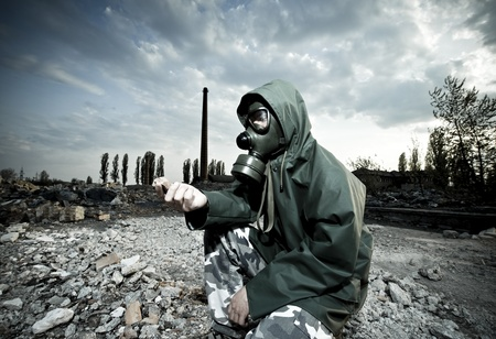 Scientist with gas mask examining rock in destroyed territory after explosion photo