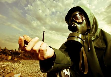 gas mask: Cient�fico con m�scara de gas examinar rock en territorio destruido despu�s de la explosi�n