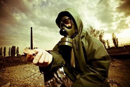 mask gas: Cient�fico con m�scara de gas examinar rock en territorio destruido despu�s de la explosi�n