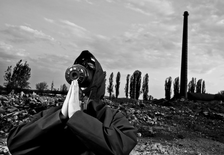 Man with gas mask praying in desolated land with ruins and pipes photo