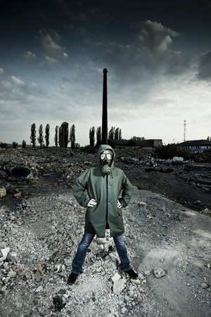 Woman in gas mask on demolished industrial background with pipes photo