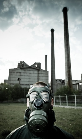 Bizarre portrait of man in gas mask on smoky industrial background with pipes after nuclear disaster Stock Photo - 9458119