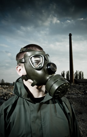 Bizarre portrait of man in gas mask on smoky industrial background with pipes after nuclear disaster Stock Photo - 9458137
