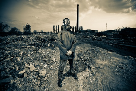Bizarre portrait of man in gas mask on smoky industrial background with pipes after nuclear disaster photo