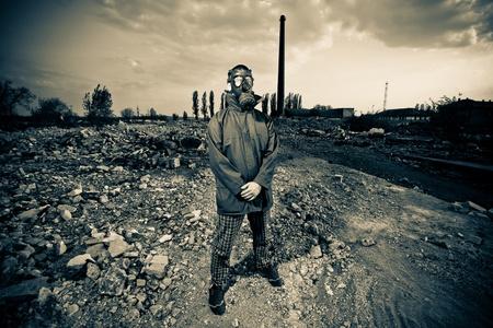 atomo: Extra�o retrato de hombre de la m�scara de gas sobre fondo industrial ahumado con tuber�as despu�s de la cat�strofe nuclear