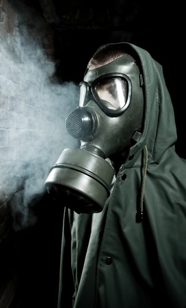 Bizarre portrait of man in gas mask on smoky industrial background with pipes after nuclear disaster Stock Photo - 9641989