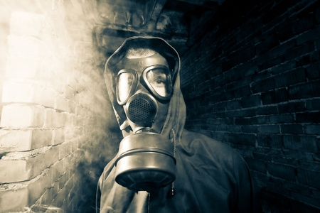 nuclear bomb: Bizarre portrait of man in gas mask on smoky industrial background with pipes after nuclear disaster