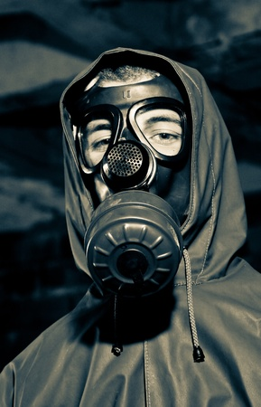 Bizarre portrait of man in gas mask on smoky industrial background with pipes after nuclear disaster  Stock Photo - 9642056