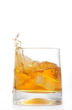 glass of whiskey with ice cubes splashing out over white  photo