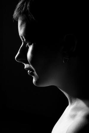 visage femme profil: Basse clé portrait d'une jeune femme