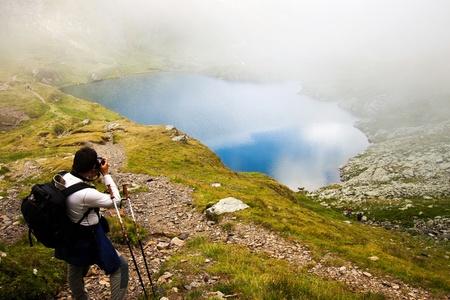 Hiker taking photos at Capra lake in Fagaras mountains, Romania Stock Photo - 10669210