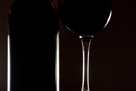 tipple: Backlit detail of a glass of red wine and the wine bottle against a solid black background
