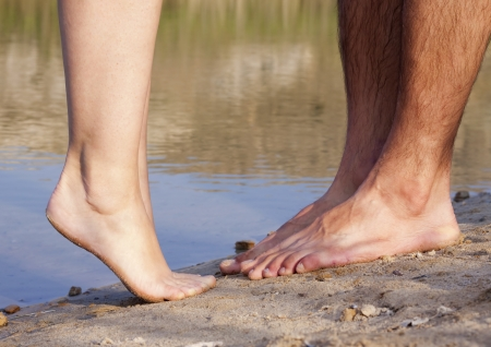 couple feet kissing near lake