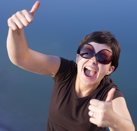 Young brunette girl with big funny sunglasses making thumbs up gesture  photo