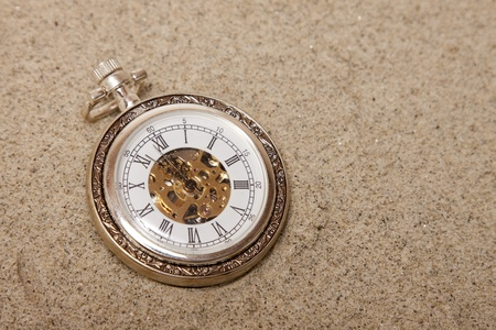 gold watch: Old pocket watch buried in sand. Lost time concept.