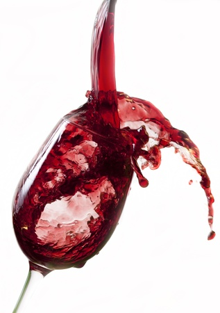 Red wine pouring into glass, isolated on white background  photo
