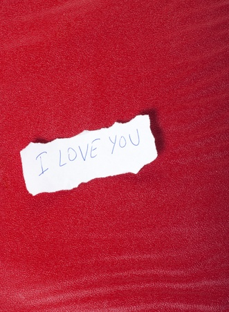 Ripped paper on red background with message of love  photo