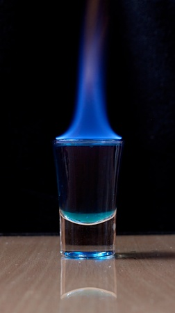 Burning drink in shot glass on a table  photo