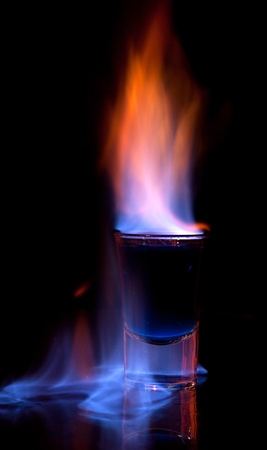 Burning drink in shot glass on a table