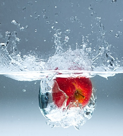 Red apple splashing into water on blue background  photo