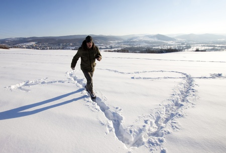 Man making big snow sign in snow  photo