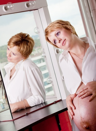 Beautiful pregnant woman daydreaming in front of a mirror Stock Photo - 12428413