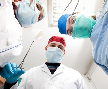 Surgeons holding medical instruments in hands and looking at patient  photo