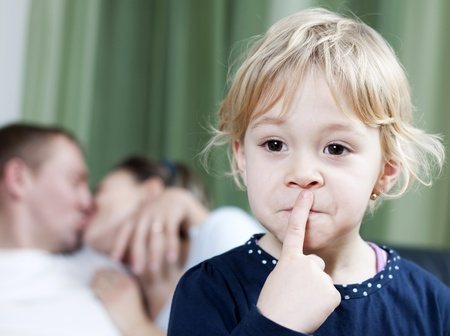 Blonde little girl making silence sign while mom and dad kissing in the background Stock Photo - 12766530