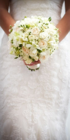 Bride holding white wedding bouquet of roses and love flower photo