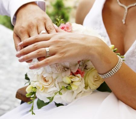 Hand van de bruidegom en de bruid met trouwringen