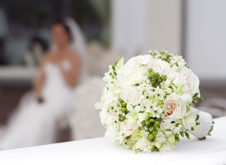 Beautiful white wedding bouquet with bride sitting in the background - shallow dof