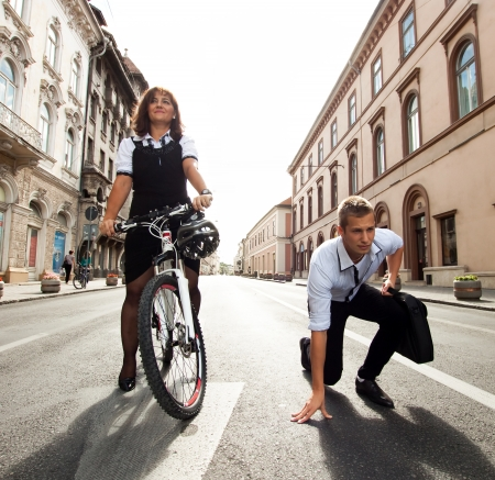 Businessman and woman racing on bikes  photo