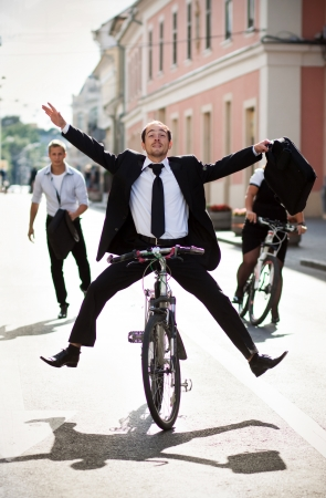 business rival: Businesspeople riding on bikes and running in city