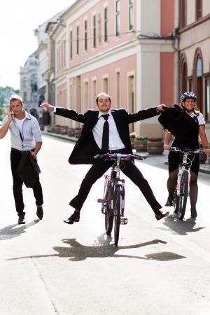 business rival: Empresarios montar en bicicleta y correr en la ciudad