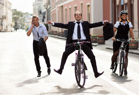 fitness goal: Businesspeople riding on bikes and running in city