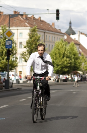 Young businessman riding a bicycle in the city