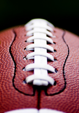 super bowl: Close up of an american football against a black background