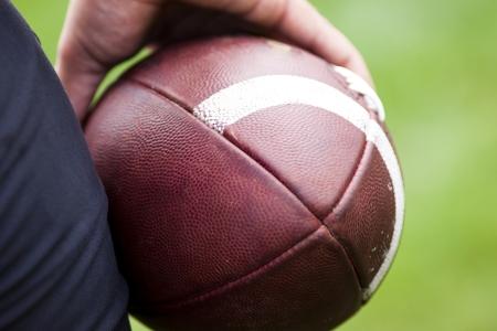 jugadores de futbol: Primer plano de una pelota de f�tbol americano contra un fondo negro Foto de archivo