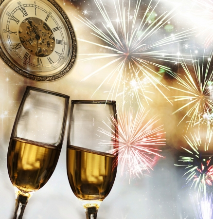Glasses with champagne against fireworks and clock close to midnight  photo