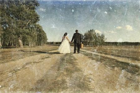 spousal: Vintage photo of newlywed couple walking away on dusty road