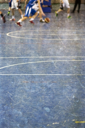 Vintage photo of school gym floor with out of focus legs of children playing basketball in the background  photo