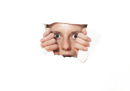 broken through: Young woman looking through torn paper hole