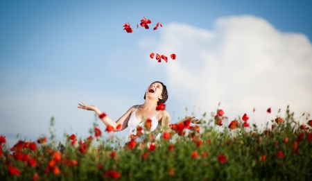 Young casual woman relaxing in poppy field photo