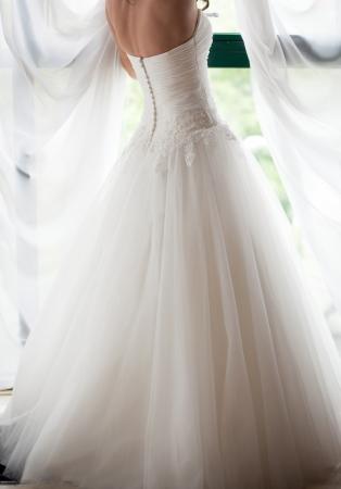 bride in white wedding dress looking in window
