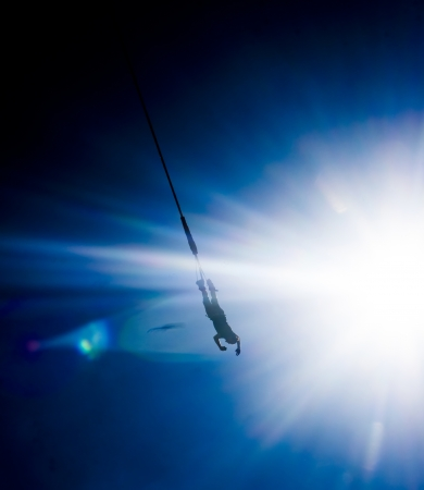 Bungee jumping - extreme sport over blue sky photo